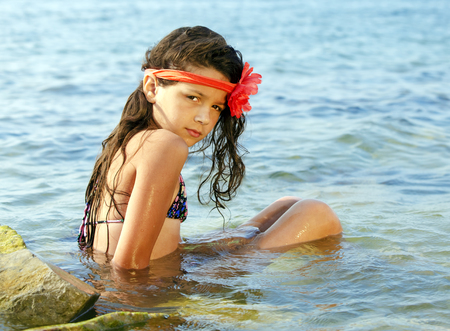Fashion girl in the water. Mysterious young girl on the sea. Beautiful girl in a swimsuit