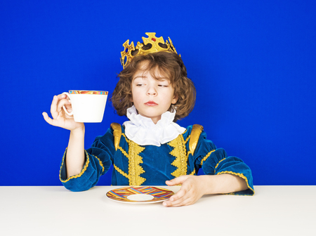 Portrait of a child in a king's clothes drinking tea on a blue background. Funny kid during a break for tea in England