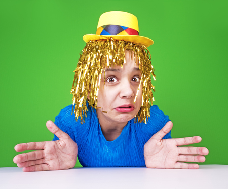 Comedy humorous joke for people. Portrait of a cute restless girl in a wig which grimaces on a green background