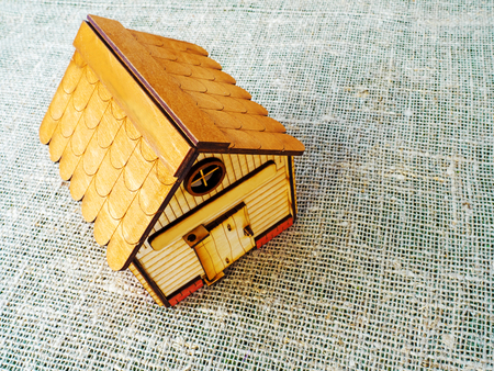 A toy wooden house on a background of burlap. The concept of an ecological habitat. Copy space Stock Photo