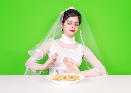 Stop the flour. The bride shows by hands the refusal of high-calorie food for the sake of his beautiful figure Stock Photo