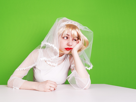 Unwanted marriage, bad life decisions concept. Serioos bride wearing white dress sitting at table and waiting for wedding, isolated on green.