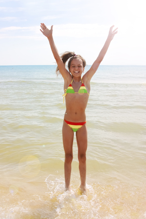 A young girl in the nature with a beautiful sea, sand and blue sky. Happy child on vacation by the sea running and jumping in the water