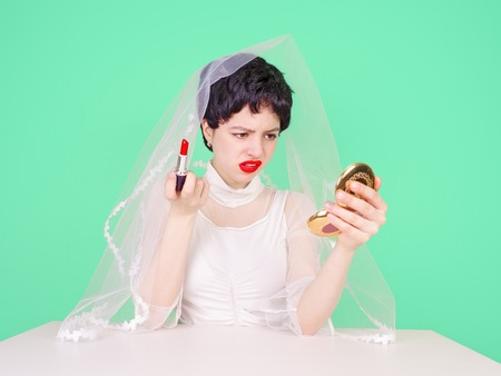 Young enraged bride teenager looking at her hairstyle in a Mirror sitting at table isolated on light background