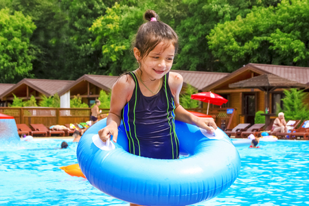 Summer vacation. Enjoying summer fun girl in blue bathing suit with an inflatable circle near the swimming pool.