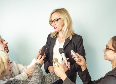 Mujer oradora pública y niñas periodistas, manos de reporteros con micrófonos de TV y grabadora de voz. Conferencia de prensa, noticias de última hora, medios de comunicación, periodismo, concepto de entrevista. Foto de archivo