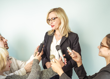 Vrouw spreker in het openbaar en meisjesjournalisten, handen van verslaggevers met tv-microfoons en spraakrecorder. Persconferentie, nieuws, massamedia, journalistiek, interviewconcept. Stockfoto