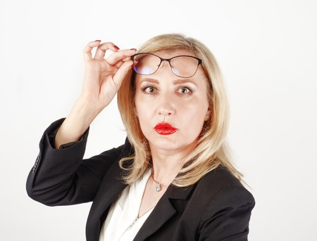 Blonde business woman in glasses and a black jacquer keeps her glasses hand looking at the camera Imagens