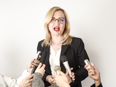 Woman Public Speaker and Hands of Reporters With TV Microphones and Voice Recorder. Press Conference, Breaking News, Mass Media, Journalism, Interview Concept.