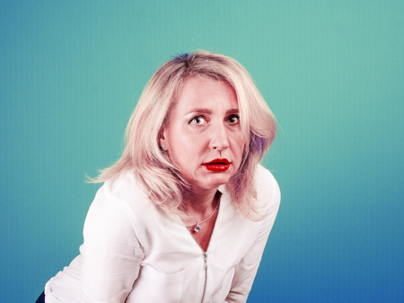 Mature blonde woman with a tired look surprised against light bright colorful background