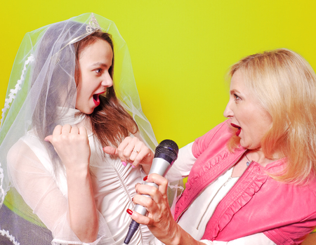 Young Singer bride and her sister with a microphone celebrating her forthcoming mariage. Studio shot. Bright colorful background.