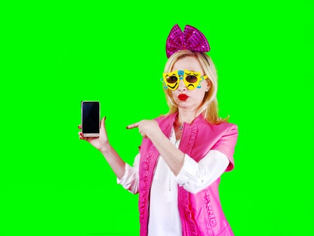 Cheerful pretty woman in carnival glasses and a pink bow, pointing with her finger to the smartphone screen, isolated on bright colorful background. Looking at the camera