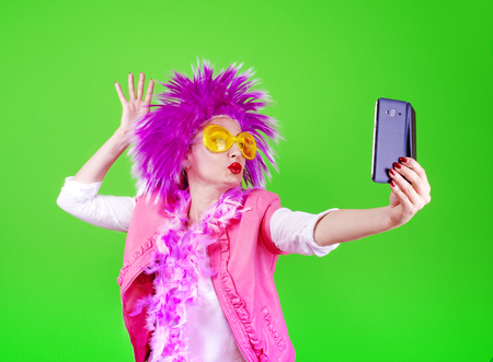 Scamper woman in a party clothes do selfie on a light background