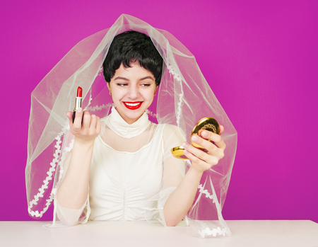 The bride paints her lips. The bride is cleaned, looking at the small mirror, sitting at the table. Pink background