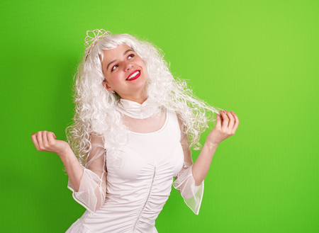 Confident and flirtatious young woman with tiara on green background