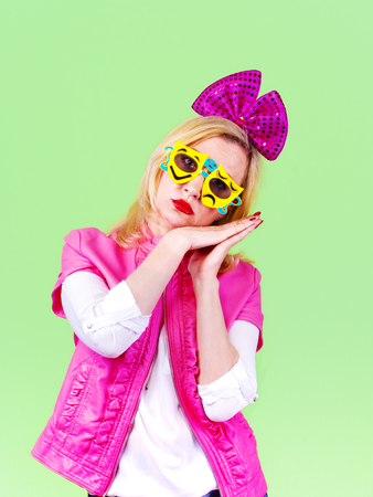 Headshot pantomime votan with a pink bow posing for camera using hands interacting sleeping, light green background Stock Photo
