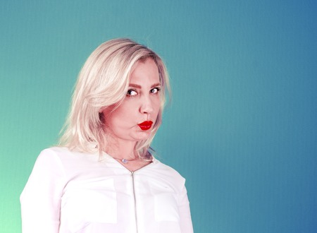Mature woman in a white blouse on a bright background. Skeptical face. Decision making