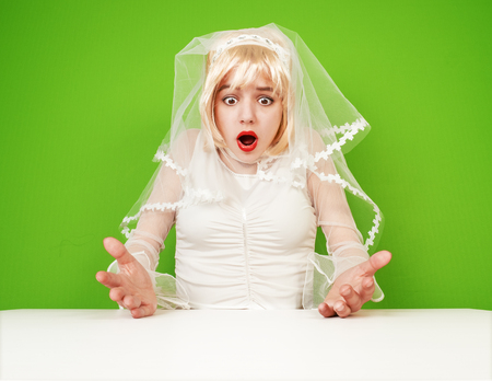 Excited beautiful blonde bride in a white dress on a green background