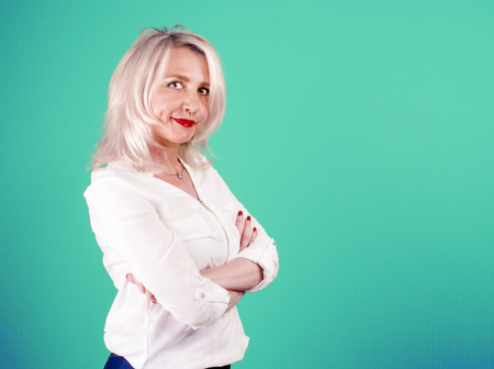 A mature woman in a white blouse crossed her arms over her chest against a bright background. Skeptical face. Decision making