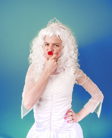 Photo of upset woman with red lips wearing white curly wig looking at camera with anger isolated over blue background Stock Photo