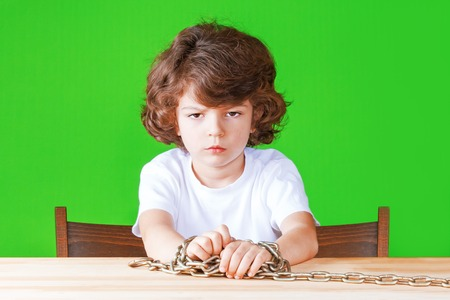 Offended little curly-headed boy in a white shirt sits at a table with chained hands. Slavery concept. Close-up. Green background.