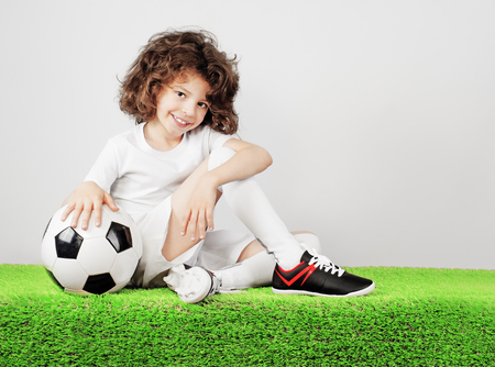 Boy with soccer ball on the green grass.