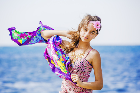 Funny young girl in a dress against the sky and the sea 스톡 콘텐츠