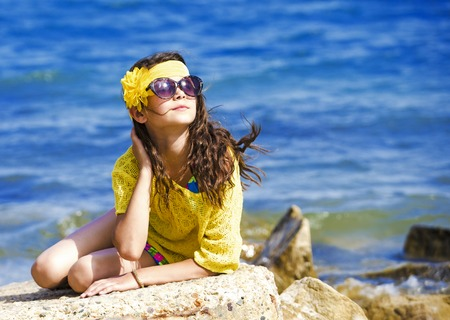 Attractive brunette teenage girl in effective attire posing on the beach by the sea or ocean Stock Photo