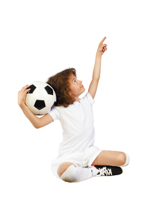 Photo of smiling preschool boy in sportswear holding soccer ball and pointing thumb up - posing on studio. Isolated on white Copy Space