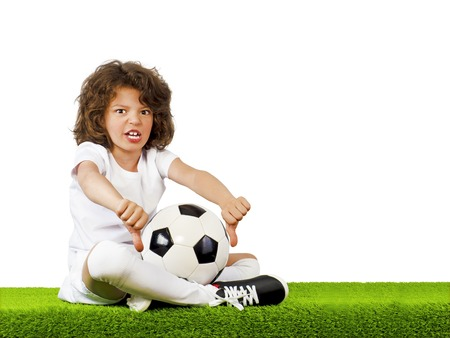 I do not like this. Bad football, judge. Little beautiful boy in uniform sitting on grass with soccer ball showing his thumbs down. Dislike. Stock Photo
