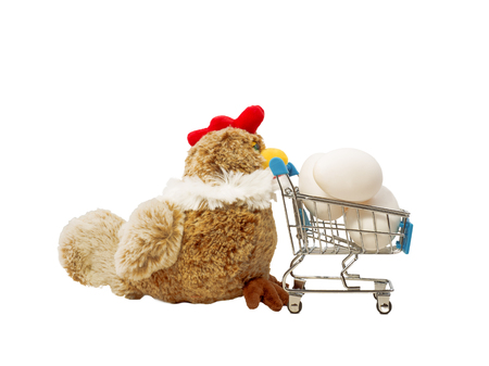 A toy chicken carries a shopping trolley with a chicken eggs. isolated on white.