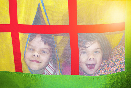 Little funny sisters pressing his noses on the mesh window of a childrens tent house looking out Stock Photo
