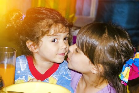 Das Mädchen küsst ihre Schwester, die am festlich gedeckten Tisch sitzt. Zwei einheimische Schwestern für immer zusammen