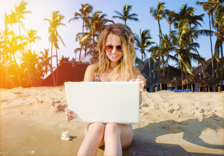 Girl with laptop on tropical beach. remote working concept 版權商用圖片