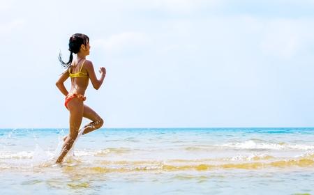 Summer fun beach woman splashing water. Panorama landscape of tropical ocean on travel holiday. Bikini girl running in freedom and joy with hands up enjoying the sun. Foto de archivo