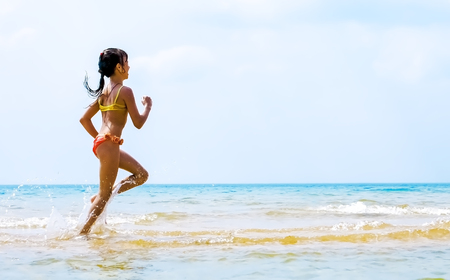 Summer fun beach woman splashing water. Panorama landscape of tropical ocean on travel holiday. Bikini girl running in freedom and joy with hands up enjoying the sun. Stockfoto