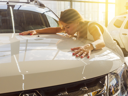 Dream about car. Gorgeous smiling woman kissing hood of new white car in the dealership.