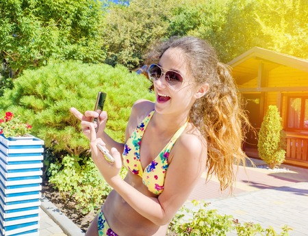 Beautiful young girl in a yellow bathing suit laughing and holding a smartphone showing an indecent gesture on a summer day.