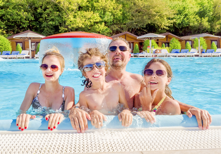 Happy family in the pool, having fun in the water, dad with three kids enjoying aqua park, beach resort, summer holidays, vacation concept