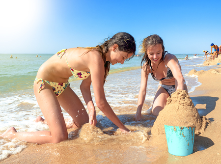 Two teen sisters making sand castle at tropical beach Banque d'images