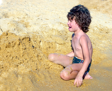Crying boy on the beach. A small child sitting by the sea and hysterically crying Stock Photo