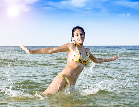 A girl jumping and immersed in a refreshing sea, ocean, on a hot summer day
