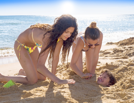 Caucasian brother and two sisters playing buried in sand at beach Stockfoto