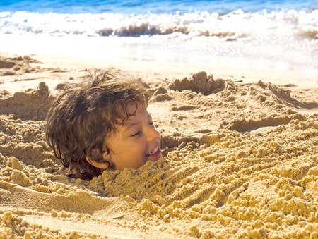the head of a funny little malchikal sticking out of the sand in the beach and her body is hiding in the sand.
