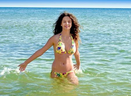 Charming girl having fun on the seashore. girl in summer swimsuit at sea Standard-Bild