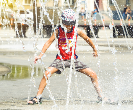 Happy kid playing in a fountain with water