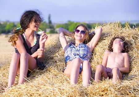 Familie sitzt auf dem Heuhaufen. Porträt eines charmanten und liebenswerten Kindes auf einem Heuhaufen an einem sonnigen Herbsttag