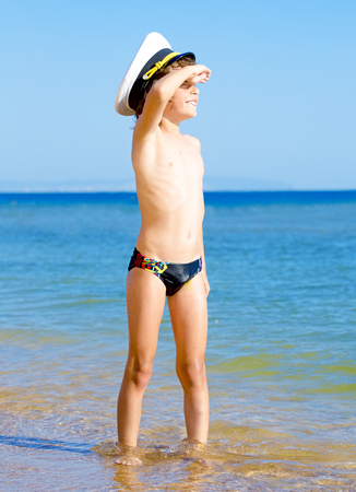 Funny child in black swimming trunks in a sea cap looking into the distance on the background of blue sea and sky