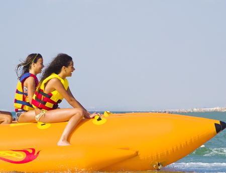 Attraktion mit extremer Geschwindigkeit im Meer. Gruppe junger Menschen, die an einem sonnigen Sommertag eine Fahrt auf einem Bananenboot genießen. Wassersport am Strand