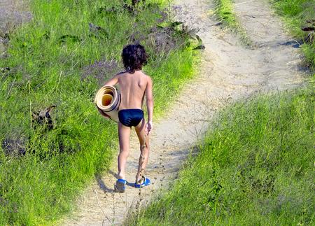 Little amusing boy with a tourist mat in hand climbing to the top of a sandy hill. 免版税图像